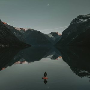 woman immersed in cold water looking at mountains